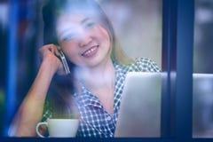 Телефон счастливой женщины Азии говоря в кафе и наслаждаться кофе Стоковая Фотография