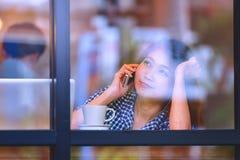 Телефон счастливой женщины Азии говоря в кафе и наслаждаться кофе Стоковое Изображение RF