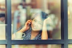 Телефон счастливой женщины Азии говоря в кафе и наслаждаться кофе Стоковое Изображение