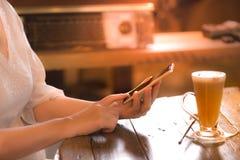 Телефон щелчка рук работницы умный на винтажной кофейне стиля стоковая фотография rf