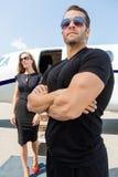 Телохранитель стоя против женщины и частного самолета Стоковое Изображение