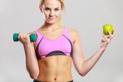 Тело диеты подходящее Девушка держит гантели и плодоовощ яблока Стоковое Изображение