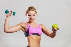 Тело диеты подходящее Девушка держит гантели и плодоовощ яблока Стоковые Фотографии RF