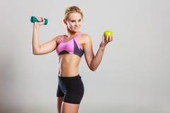 Тело диеты подходящее Девушка держит гантели и плодоовощ яблока Стоковые Изображения