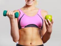 Тело диеты подходящее Девушка держит гантели и плодоовощ яблока Стоковая Фотография RF