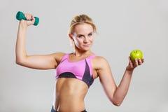 Тело диеты подходящее Девушка держит гантели и плодоовощ яблока Стоковое Изображение RF