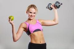 Тело диеты подходящее Девушка держит гантели и плодоовощ яблока Стоковые Изображения RF