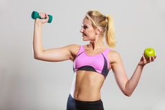 Тело диеты подходящее Девушка держит гантели и плодоовощ яблока Стоковая Фотография