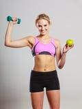 Тело диеты подходящее Девушка держит гантели и плодоовощ яблока Стоковые Фото