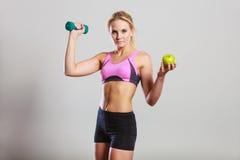 Тело диеты подходящее Девушка держит гантели и плодоовощ яблока Стоковое Фото