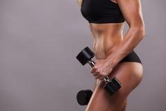 Тело крупного плана женщины фитнеса с гантелями Sporty девушка показывая ее вышколенное тело Изолировано на серой предпосылке Стоковое Изображение