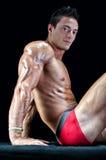 Тело привлекательного показа молодого человека нагого мышечное, усаживание на поле Стоковые Фото