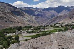 Тибетская деревня в высоких горах долины: среди утесов коричневого цвета и барда на дне ущелья протяните зеленый str Стоковое Изображение