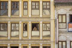 Тибетская женщина смотрит вне окно желтого многоэтажного здания стоковые фото