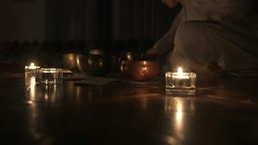Тибетские шары петь Женщина играет музыку в темноте на шарах петь candlelight сток-видео