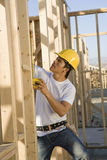 Тимберс работника измеряя на строительной площадке Стоковое фото RF