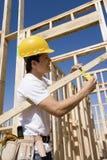 Тимберс рабочий-строителя измеряя Стоковая Фотография