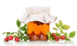 Тинктура плодов шиповника и свежих ягод изолированных на белизне Стоковое Фото