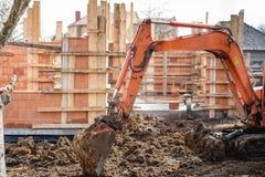 типа След деятельность и загрузка затяжелителя экскаватора на строительной площадке дома стоковое фото rf