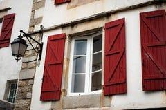 Типичные Белые Дома с красным цветом покрасили штарки окна стоковое фото