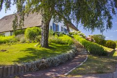 Типичный голландский дом с крышей соломы, с зеленым садом Стоковая Фотография RF