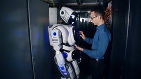 Типы инженера на мониторе робота Программист и стойка droid в комнате сервера, получая готовый для работы сток-видео