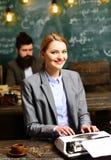 Тип бизнес-леди на винтажной машинке с запачканным человеком на предпосылке Чувственная девушка typewrite исследование Счастливый Стоковые Изображения RF