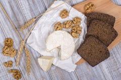 Тип бри сыра Сыр камамбера Свежий сыр бри и кусок на деревянной доске с грецкими орехами и куском черного хлеба итальянско стоковые фото