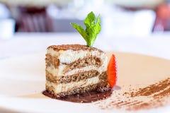 Тирамису на белой запачканном плитой эспрессо торта предпосылки стоковое фото