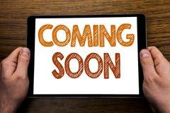 Титр текста сочинительства руки приходя скоро Концепция дела на будущее сообщения написанное на компьтер-книжке таблетки, деревян Стоковое Изображение RF