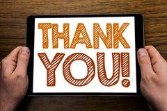 Титр текста сочинительства руки спасибо Концепция дела для сообщения спасибо написанного на компьтер-книжке таблетки, деревянной  Стоковые Фотографии RF