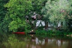 Тихое место на воде с красными шлюпкой, коттеджем и деревьями внутри Стоковое Изображение RF