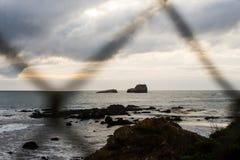 Тихоокеанское побережье через загородку звена цепи стоковое фото