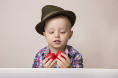 4-ти летний мальчик в шляпе и рубашке держа пасхальные яйца рук красные, Стоковые Фотографии RF