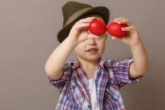 4-ти летний мальчик в шляпе и рубашке держа пасхальные яйца рук красные, Стоковое Изображение RF