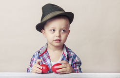 4-ти летний мальчик в шляпе и рубашке держа пасхальные яйца рук красные, Стоковые Изображения