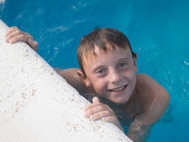 9-ти летний мальчик имея потеху в бассейне Стоковое фото RF