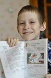10-ти летний мальчик сидит при учебник, делая домашнюю работу. Стоковая Фотография