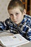 10-ти летний мальчик с разрывами в глазах сидит перед textb Стоковые Изображения RF