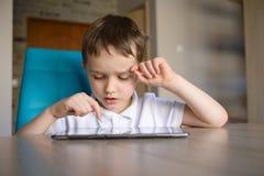 6-ти летний ребенок используя таблетку пока сидящ на таблице Стоковые Фото