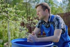 30-ти летний человек отдыхая на земле в парнике Стоковые Изображения