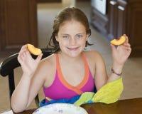 10-ти летняя девушка сидя на таблице держа кусок персика в каждой руке Стоковое фото RF