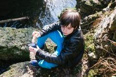 12-ти летний мальчик есть сандвич снаружи в природе Стоковые Фото
