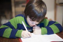 6-ти летний ребенок выполняет домашнюю работу Стоковое Фото