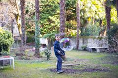 7-ти летний ребенок outdoors в саде в зиме делает большое мыло Стоковая Фотография