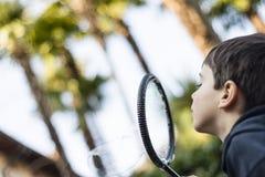 7-ти летний ребенок outdoors в саде в зиме делает большое мыло Стоковое фото RF