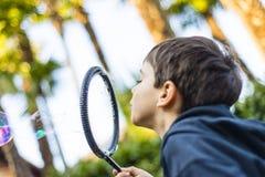 7-ти летний ребенок outdoors в саде в зиме делает большое мыло Стоковые Фотографии RF