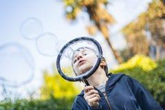 7-ти летний ребенок outdoors в саде в зиме делает большое мыло Стоковые Изображения