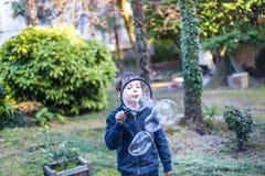 7-ти летний ребенок outdoors в саде в зиме делает большое мыло Стоковая Фотография RF