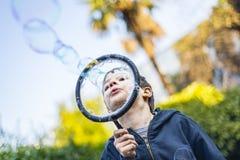 7-ти летний ребенок outdoors в саде в зиме делает большое мыло Стоковое Изображение